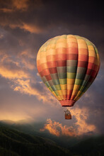 Rabbit And Deer In A Multi Coloured Hot Air Balloon Rising Above Hills Towards A Stormy Sky