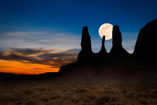Moon Rising Behind A Silhouette Of Three Sisters, Monument Valley, Arizona, USA