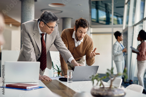 Mature businessman discusses with younger colleague who works on computer during internship at corporate office.