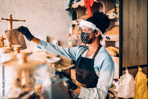 African American middle aged female worker with shield and protective mask on face working in bakery. Coronavirus, Covid-19 concept.