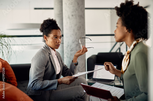 Fototapeta Black female business mentor talks about work assignments with a trainee during the meeting. obraz