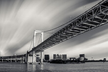 View Of Rainbow Bridge In Tokyo Against Cloudy Sky