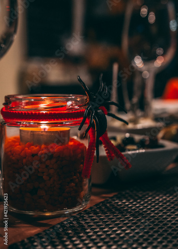 Canvas Print Close-up Of Decorating Spider In Glass Jar On Table