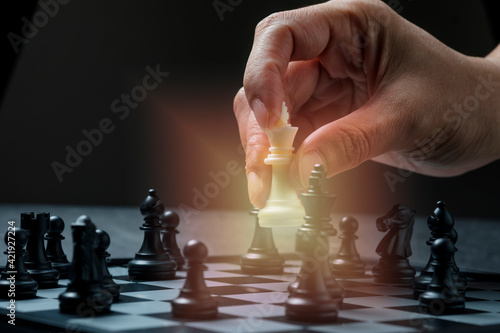 Stampa su Tela A Hand Playing Chess Game Holding Knight Chess Piece With Orange Light In Dark B