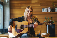 Front View Portrait Of Adult Caucasian Woman Sitting At Empty Cafe With Guitar On Her Lap Looking To The Camera - Female Musician Relaxed Real People Leisure Concept