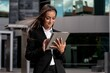 Young Hispanic businesswoman in a suit working on a tablet in front of a modern office building