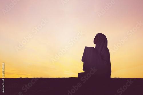 Carta da parati Silhouette of devout woman pray to the Allah on hill