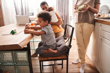 Man And His Children Sitting At The Table And Playing With Rubber Ducks