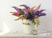 Bouquet Of Lupines And A Metal Alarm Clock