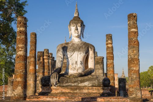 Fotografie, Obraz Sculpture of a seated Buddha on the ruins of a Bujjist temple on a sunny evening