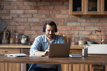 Focused Young Caucasian Man In Headphones Work Online On Computer At Home Kitchen. Millennial Male In Earphones Look At Laptop Screen Study Or Take Distant Course On Internet. Virtual Event Concept.