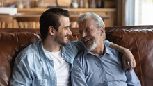 Overjoyed Mature Caucasian Father And Happy Young 20s Man Child Sit Relax On Couch In Living Room Talking Chatting. Smiling Elderly Dad And Adult Grownup Son Rest On Sofa At Home Enjoy Family Time.