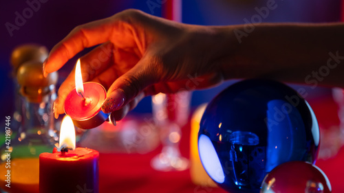 Fotografie, Tablou Crop witch burning candles near crystal ball