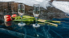 There Are Two Glasses Of Champagne On The Blue Transparent Ice With Deep Cracks. Nearby Are Bright Red And Yellow Tulips. Snow In The Distance. Reflection