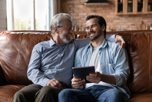 Overjoyed Caucasian Adult Man Child Relax On Sofa At Home With Mature Modern Dad Use Tablet Together. Smiling Young Adult Grownup Son Hold Pad Rest On Couch In Living Room With Elderly Father.