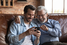 Smiling Mature Grey-haired 60s Father And Grownup Son Relax On Sofa At Home Browse Smartphone Together. Happy Older Caucasian Dad And Adult Man Child Have Fun Use Cellphone Talk On Call Online.