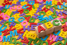 Alphabet On Wooden Tiles And ABC On A Cube Against Yellow Background. Concept Of Child Leraning Education Development