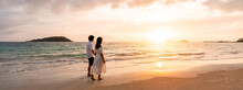 Young Woman Traveler Holding Man's Hand And Looking Beautiful Sunset On The Beach, Couple On Vacation In Summer Concept