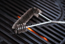 Cleaning Outdoor Gas Grill With A Metal Brush Before Next Grilling. Close-up.