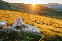 Rising Sun Over The Sinjal Or Dinara (1831 M) Mountain - The Highest Point Of Croatia In The Dinaric Alps On The Border Between Croatia And Bosnia And Herzegovina. Hiking Trail Mark Painted On Rock.