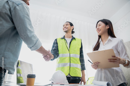 team of young architect start up business planning concept, group of successful engineer people shake hand after success discussion construction work with coworker during creative design meeting
