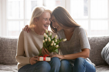 Loving young adult female child congratulate excited elderly mother with birthday anniversary at home. Smiling caring grownup millennial daughter present gift flowers to old mom on women s day.
