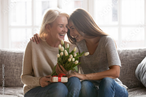 Fototapeta Loving young adult female child congratulate excited elderly mother with birthday anniversary at home. Smiling caring grownup millennial daughter present gift flowers to old mom on women s day. obraz