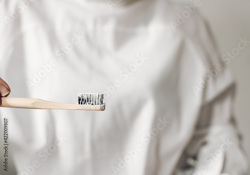 Fotografija A female hand holds a bamboo toothbrush with tooth powder