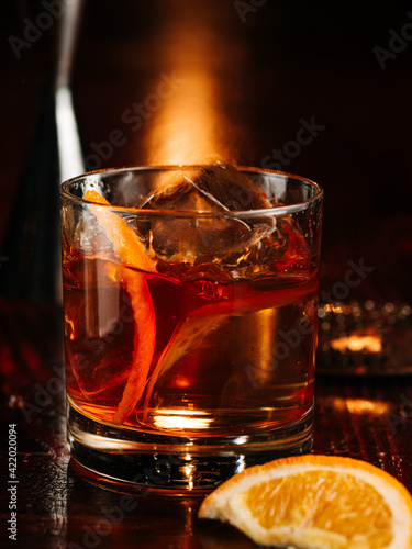 Fotografie, Obraz a glass of whiskey with an ice cube and orange peel decor