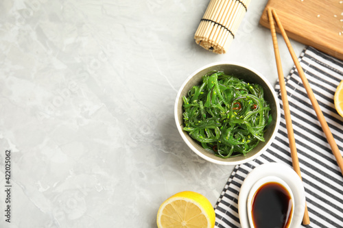 Fototapeta Japanese seaweed salad served on light marble table, flat lay. Space for text obraz
