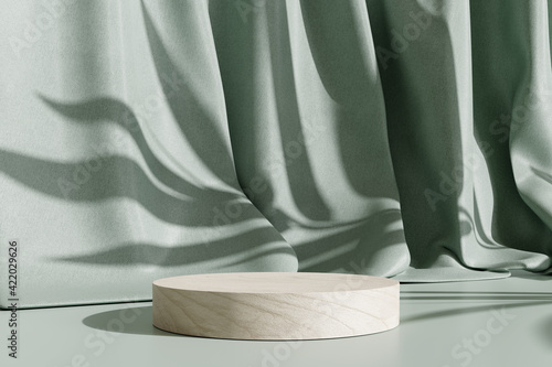 Wooden product display podium stand with shadow nature leaves on green curtain background. 3D rendering