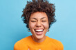 Close up shot of beautiful young African American woman with natural curly hair smiles broadly has positive look at camera being in good mood wears orange jumper isolated over blue background