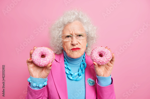 Fototapeta Dissatisfied wrinkled senior woman holds two delicious doughnuts eats junk food wears stylish outfit isolated over pink background. Elderly lady with tasty dessert indoor. Stylish grandmother obraz