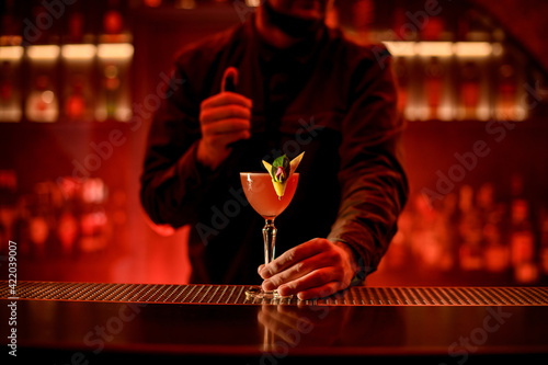 Fototapeta man bartender holds with his hand glass with bright alcoholic cocktail on bar counter. obraz