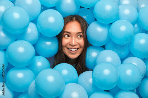 Fotografie, Obraz Smiling good looking young woman with dark hair enjoys holiday celebration looks aside thoughtfully surrounded by many inflated blue balloons expresses good emotions