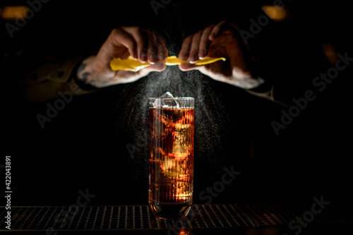 Fototapeta magnificent view of glass of drink standing on bar and man's hand sprinkling on