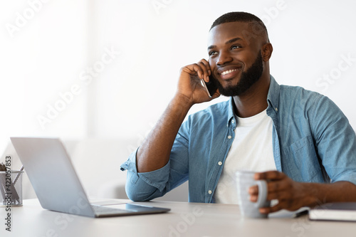 Successful black freelancer guy having coffee break at workplace in home office