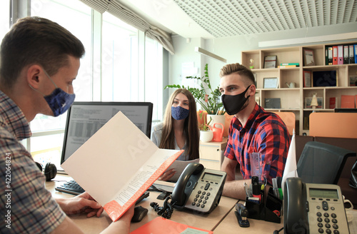 Successful lawyer in protective mask giving consultation to family couple about buying house Wallpaper Mural