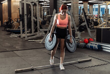 Strong Muscular Red-haired Woman With Barbell Disks In Her Hands. Intense, Functional Training