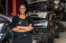 A Black Woman Who Owns A Business Stands With Arms Folded, Smiling And Looking At The Camera On Blur Factory Background. A Black Worker Stands At The Auto Parts Factory In Business Onwner Concept.