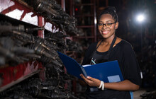 A Black Woman, Business Owner Or Employee In A Factory Engine Parts. Holding The File To Check The Product List. Smiling And Looking At The Camera N Business Onwner And Worker Concept.