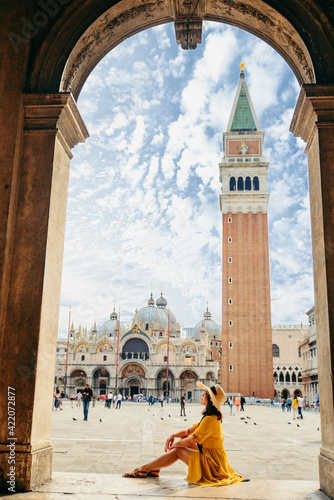 woman sitting on stairs resting looking at saint marco piazza at sunny summer da Fototapet
