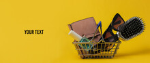 Minimalistic Shopping Concept. Mini Shopping Basket With Female Accessories On Yellow Background. Copy Sapce