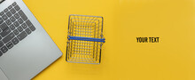 Online Shopping Concept. Laptop And Mini Shopping Basket On Yellow Background. Copy Space