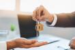 Leinwandbild Motiv close up view hand of property realtor / landlord giving key house to buyer / tenant..