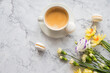 Macaroons with white cup of coffee, bright beautiful flowers on marble background.Beautiful breakfast for woman. Spring concept.Copy space
