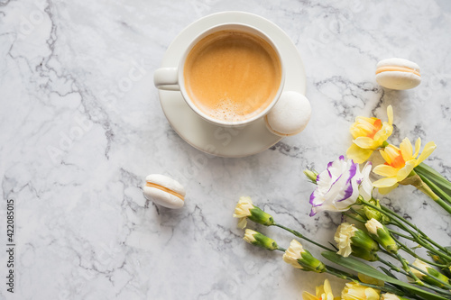 Fototapeta Macaroons with white cup of coffee, bright beautiful flowers on marble background.Beautiful breakfast for woman. Spring concept.Copy space obraz