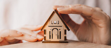 Woman Holds And Protects A Wooden House With Her Hands With The Sun On A Light Pink Background. Sweet Home