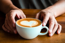 Hands Of A Man Or Barista Holding Cup Of Hot Coffee Latte With Heart Shaped Foam Art