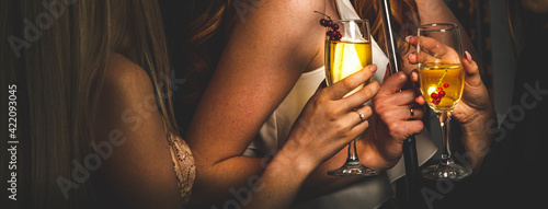 Tela glass of champagne in woman hand at a party